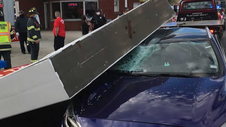 Man suffers concussion after car is hit by falling gas station sign