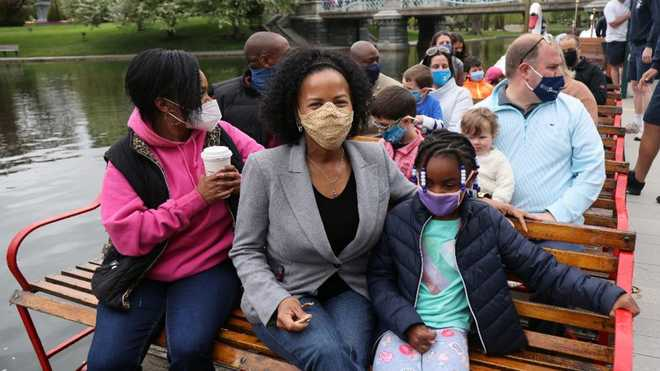 Boston Mayor Kim Janey, center, takes a ride on a Swan Boat with her family to celebrate the 144th anniversary of the Boston Swan Boats at the Boston Public Garden lagoon on May 8, 2021.