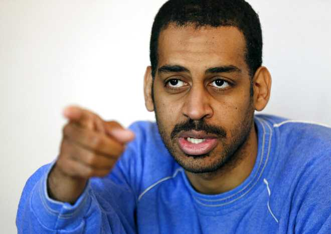 """FILE - In this Friday, March 30, 2018, file photo, Alexanda Amon Kotey, allegedly among four British jihadis who made up a brutal Islamic State cell dubbed """"The Beatles,"""" speaks during an interview with The Associated Press at a security center in Kobani, Syria. Kotey, one of two British nationals charged with joining with the Islamic State group and conspiring to torture and behead American and European hostages in Syria, is scheduled to plead guilty to criminal charges, Thursday, Sept. 2, 2021, in U.S. District Court in Alexandria, Va. (AP Photo/Hussein Malla, File)"""