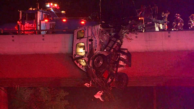 Cab of truck left dangling over I-495 overpass after crash